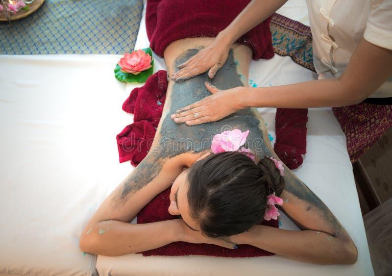 De masseur die massage spa doen met behandelingsmodder op Aziatisch vrouwenlichaam in de Thaise kuuroordlevensstijl, ontspant zo  royalty-vrije stock afbeeldingen