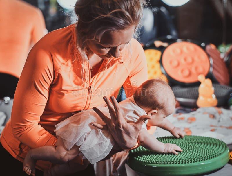 De masseur doet massage met ortophedic stuk speelgoed voor weinig baby stock afbeelding