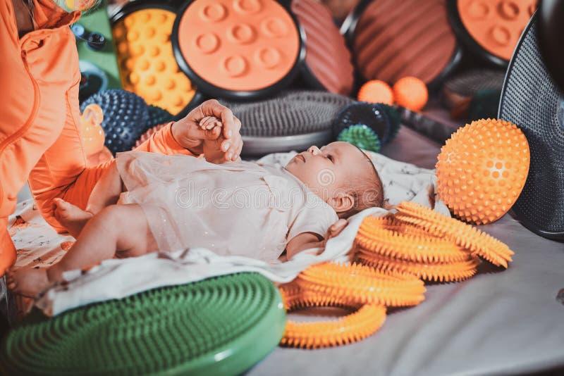 De masseur doet massage met ortophedic stuk speelgoed voor weinig baby royalty-vrije stock afbeeldingen