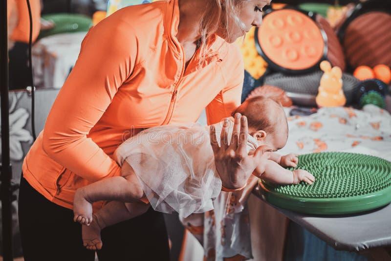 De masseur doet massage met ortophedic stuk speelgoed voor weinig baby royalty-vrije stock fotografie