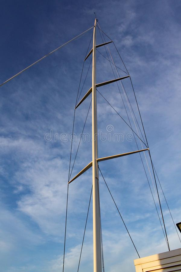 De mast en het optuigen van een het rennen jacht komen tegen de duidelijke blauwe hemel duidelijk uit stock fotografie