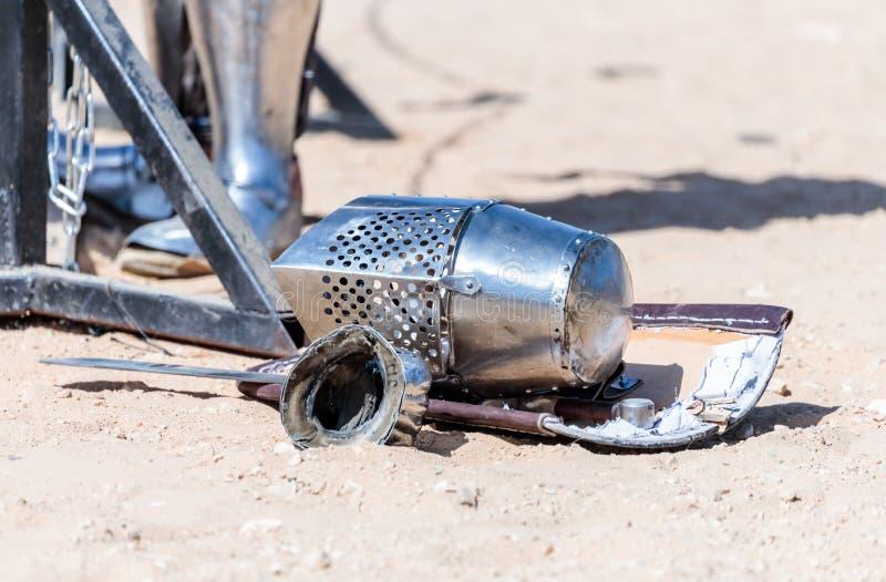 De materiaalridder - de deelnemer in het ridderfestival - schild, zwaard, helm en handschoen ligt op de grond dichtbij de lijsten royalty-vrije stock afbeeldingen