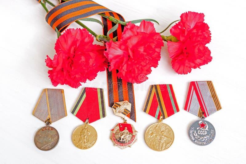 9 de mayo fondo festivo de Victory Day - medalla del jubileo de la gran guerra patriótica con los claveles y la cinta rojos de Sa foto de archivo libre de regalías