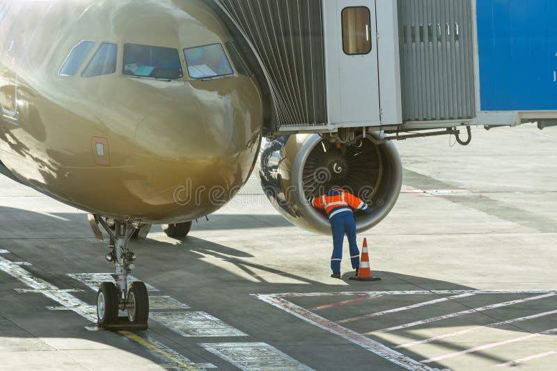De mechanische ingenieursarbeider controleert de motorventilator van vliegtuig vóór vertrek van luchthaven stock fotografie