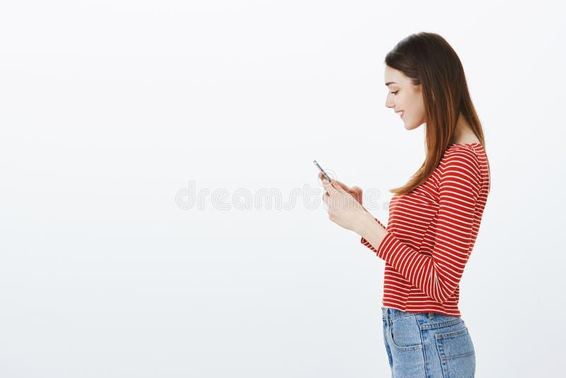 De mededeling is pret Profielschot van tevreden charmante gelukkige vrouw die in gestreepte blouse, smartphone, het typen houden royalty-vrije stock foto's