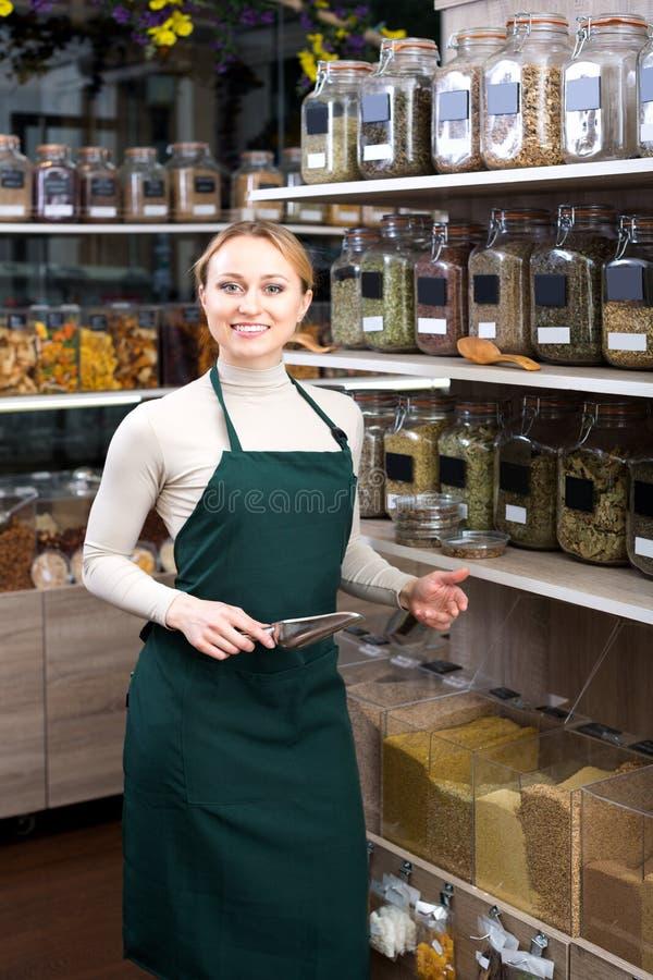 De medewerker die van de vrouwenwinkel zich naast organisch voedsel bevinden stock foto's
