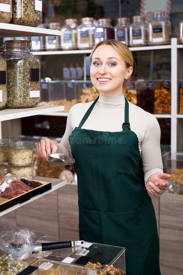 De medewerker die van de vrouwenwinkel zich naast organisch voedsel bevinden stock fotografie