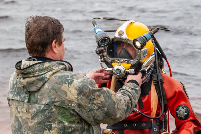 De medewerker helpt de duiker om op de helm te zetten Het diepzeewerk royalty-vrije stock afbeeldingen