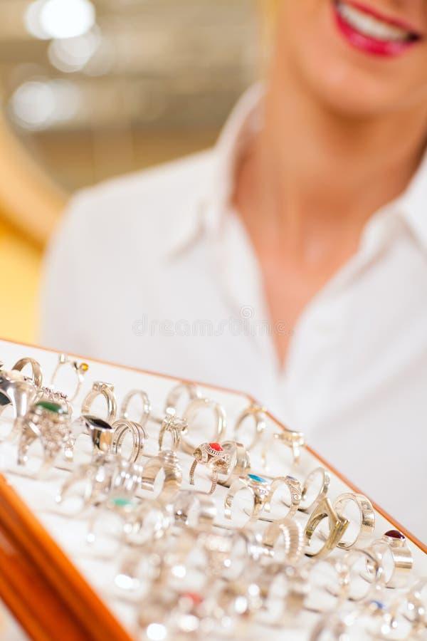 De medewerker van de winkel bij de juwelier stock fotografie