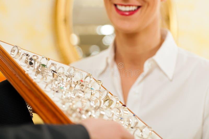 De medewerker van de winkel bij de juwelier stock foto's