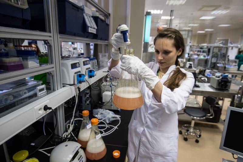 De medewerker van het vrouwenlaboratorium met fles in van hem dient biochemie in stock foto's