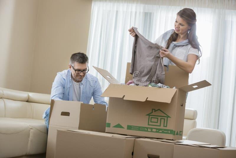De medio-volwassen dozen van het paar uitpakkende karton in nieuw huis stock foto's