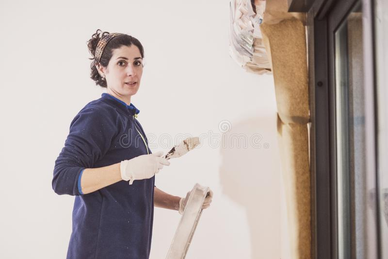 De medio volwassen vrouw schildert de ruimten van haar huisruimten royalty-vrije stock fotografie