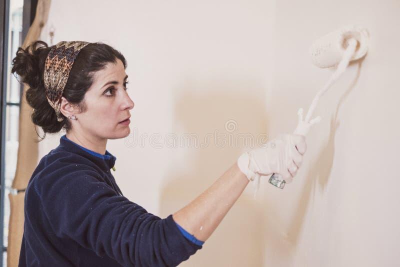 De medio volwassen vrouw schildert de ruimten van haar huisruimten stock afbeelding