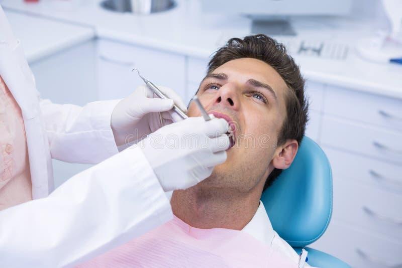 De medische apparatuur van de tandartsholding terwijl het geven van behandeling aan de mens royalty-vrije stock afbeeldingen