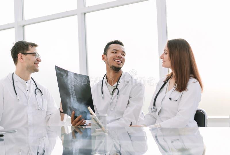 De medische collega's bespreken röntgenstraal, zittend bij de bureaulijst stock afbeeldingen