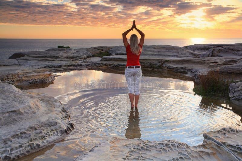 De meditatie van de vrouwenyoga door de oceaanzonsopgang stock fotografie