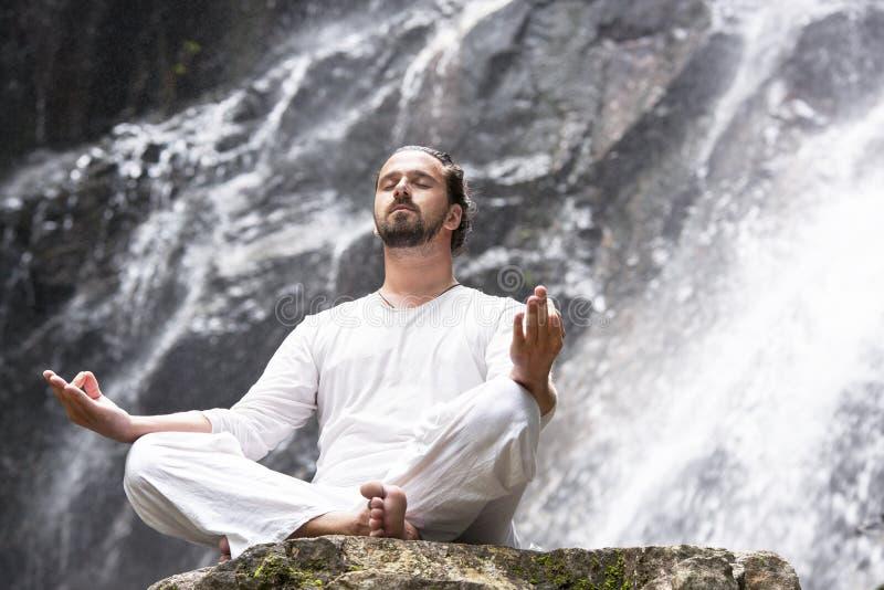De meditatieconcept van de Wellnessyoga Jonge mensenzitting in lotusbloempositie inzake de rots onder tropische waterval royalty-vrije stock foto