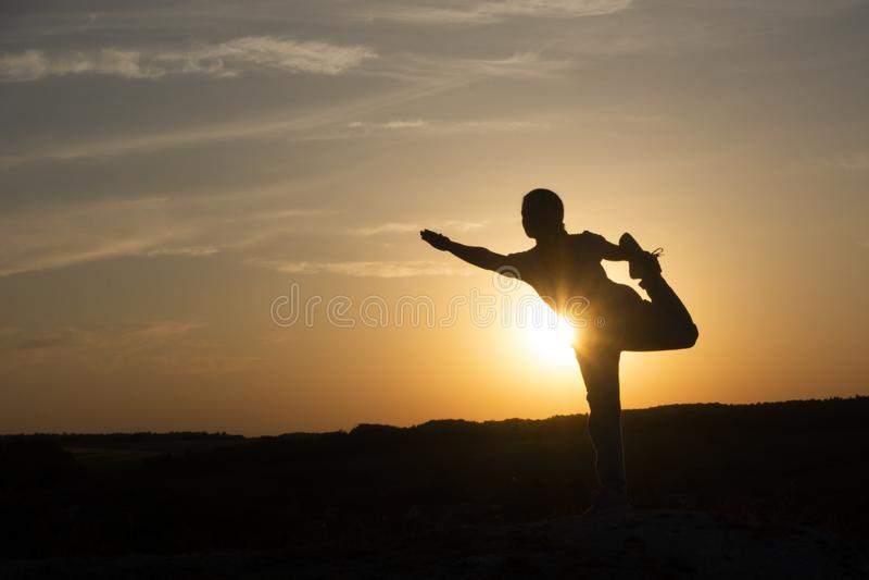 De meditatiemeisje van het yogasilhouet op de achtergrond van de zonsondergang, de geschiktheid en de gezonde levensstijl stock afbeeldingen