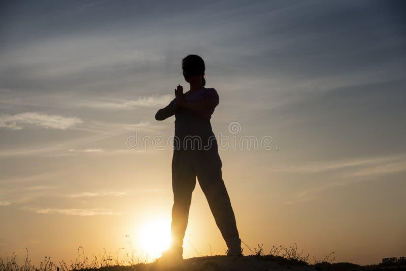 De meditatiemeisje van het yogasilhouet op de achtergrond van de zonsondergang, de geschiktheid en de gezonde levensstijl royalty-vrije stock foto's