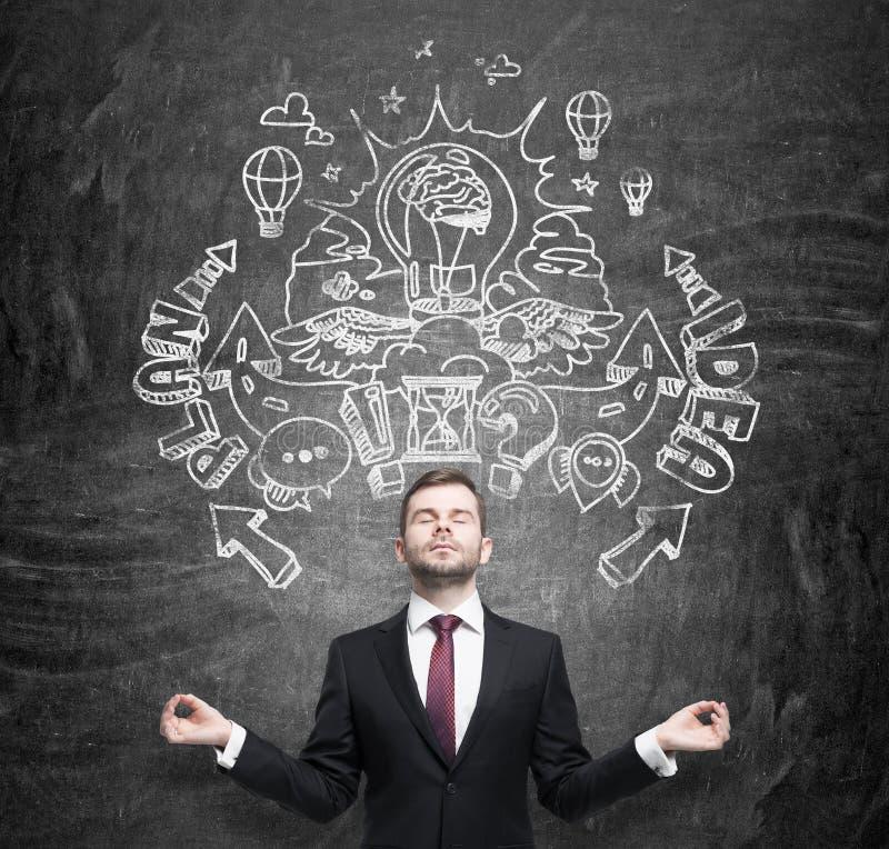 De meditatieve zakenman droomt over een uitvinding van nieuwe bedrijfsideeën voor bedrijfsontwikkeling businessplan en idee sketc stock foto's