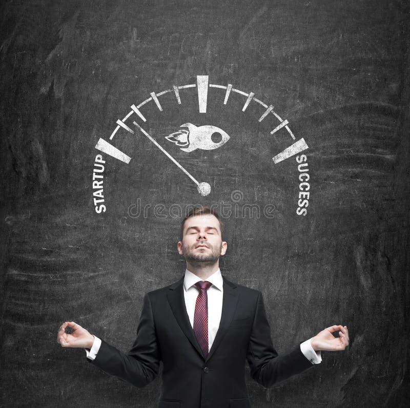 De meditatieve zakenman ontwikkelt een succesvol startproject Een geschetste schaal op het zwarte bord dat op p wijst stock foto