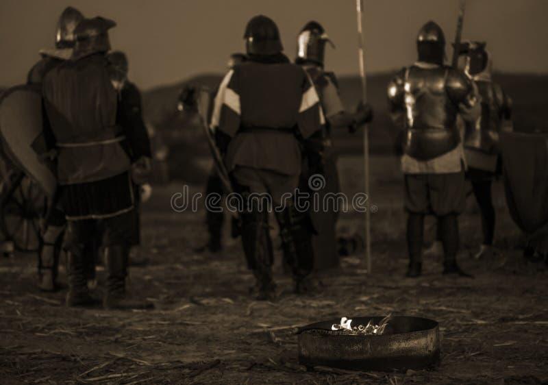 De Medivalmilitairen bij een kamp steken in brand stock afbeeldingen