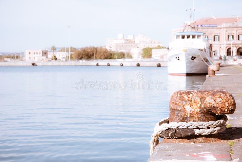 De meertroskabel met een geknoopt eind bond rond cleat op een cementpijler Zeevaart royalty-vrije stock foto