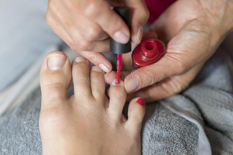 De meester behandelt de spijkers van de klant met vernis Dient handschoenenzorgen over de voetspijkers van een vrouw in Pedicure, royalty-vrije stock fotografie