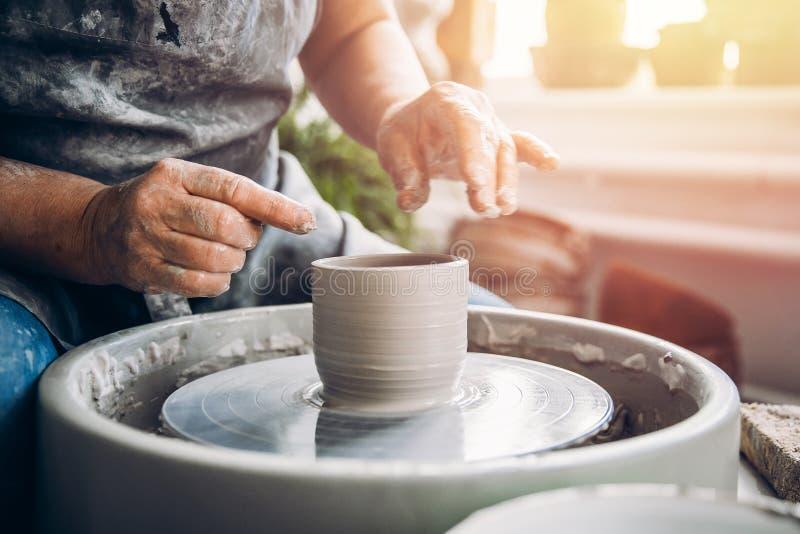 De meester houdt pot die van klei op pottenbakkerswiel wordt gemaakt royalty-vrije stock afbeelding