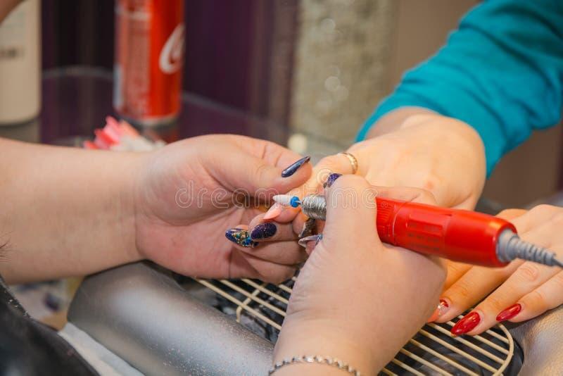 De meester in de schoonheidssalon doet manicure stock foto
