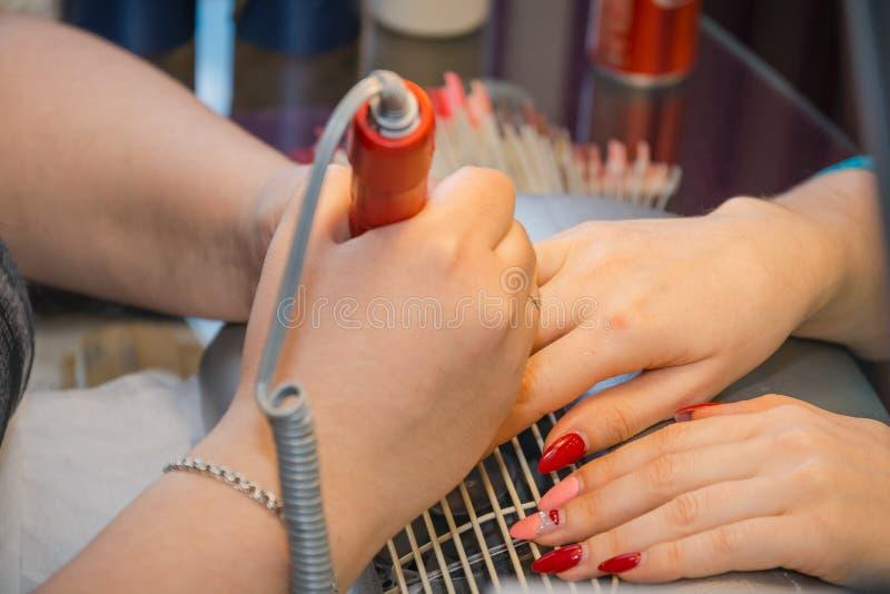 De meester in de schoonheidssalon doet manicure royalty-vrije stock foto