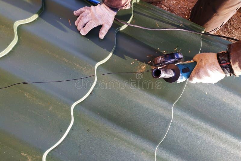 De meester snijdt een professioneel metaalblad voor installatie op het dak van het huis royalty-vrije stock afbeeldingen