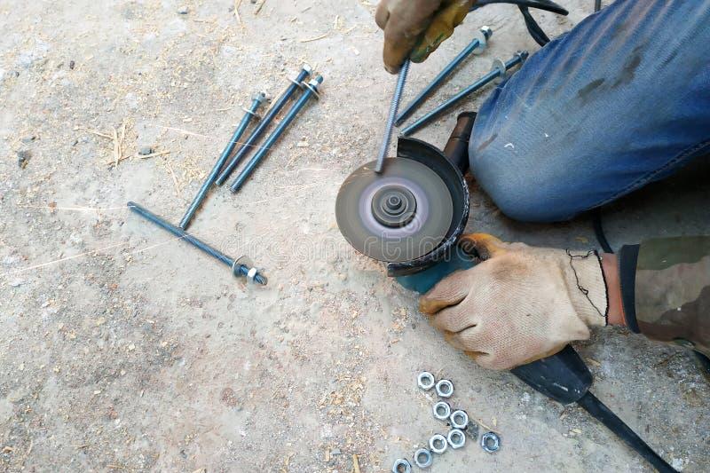 De meester snijdt en bout de bouten vast gebruikend een hoekmolen stock foto