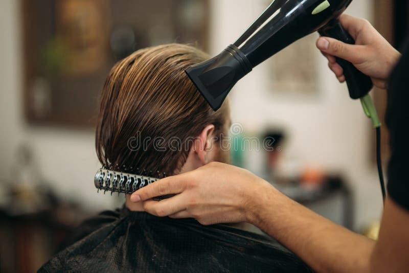 De meester snijdt haar en baard van mensen in de herenkapper en gebruikt een droogkap stock foto
