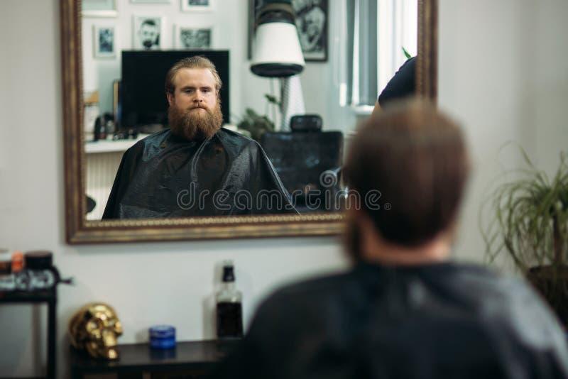 De meester snijdt haar en de baard van mensen in de herenkapper, kapper maakt kapsel voor een jonge mens stock afbeelding