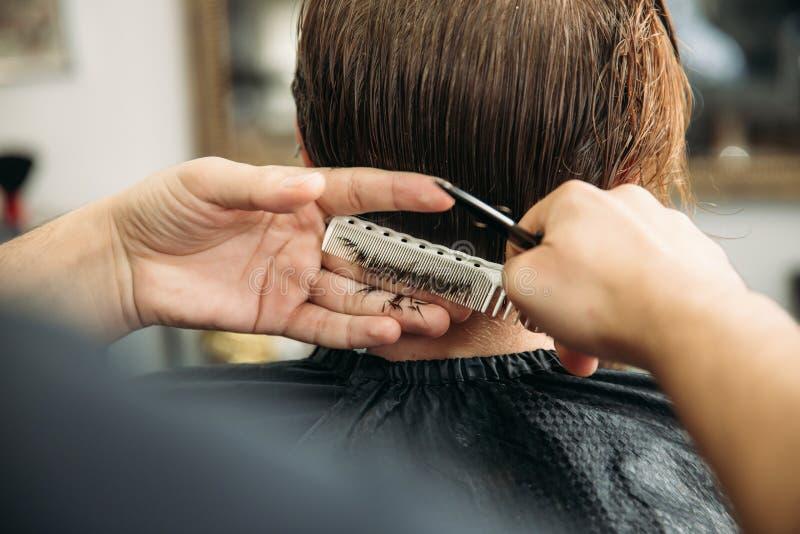 De meester snijdt haar en de baard van mensen in de herenkapper, kapper maakt kapsel voor een jonge mens stock fotografie