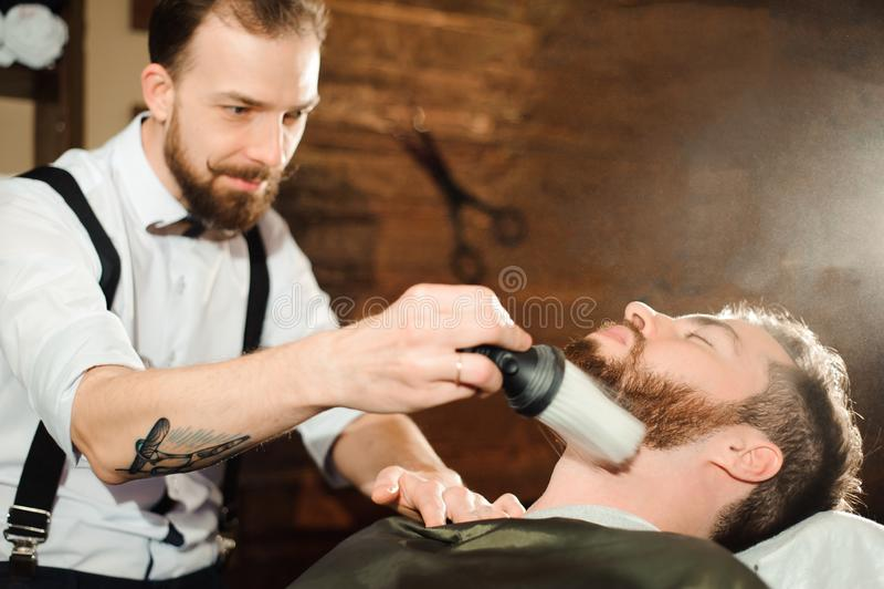 De meester snijdt haar en baard van mensen in de herenkapper stock afbeeldingen