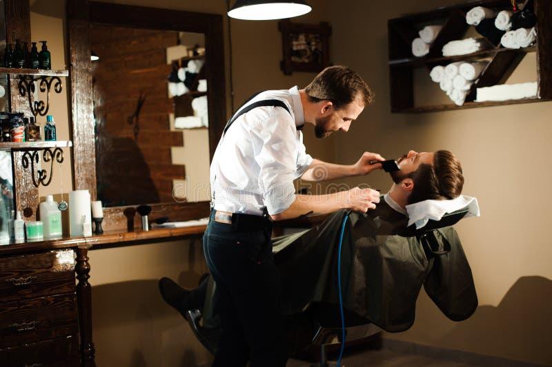 De meester snijdt haar en baard van mensen in de herenkapper stock foto
