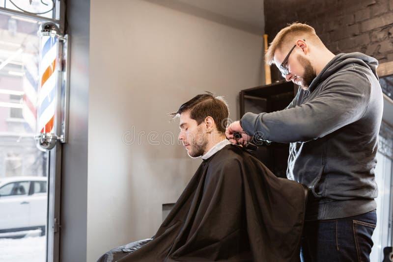 De meester snijdt haar en de baard van mensen in de herenkapper, kapper maakt kapsel voor een jonge mens Het kapperswerk met stock afbeeldingen