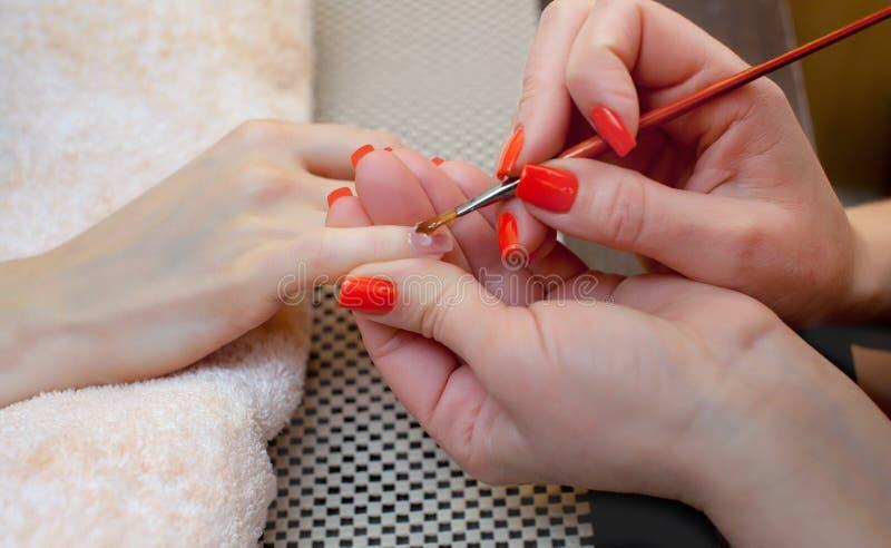 De meester van manicure maakt het gel van spijkeruitbreidingen in de schoonheidssalon stock foto