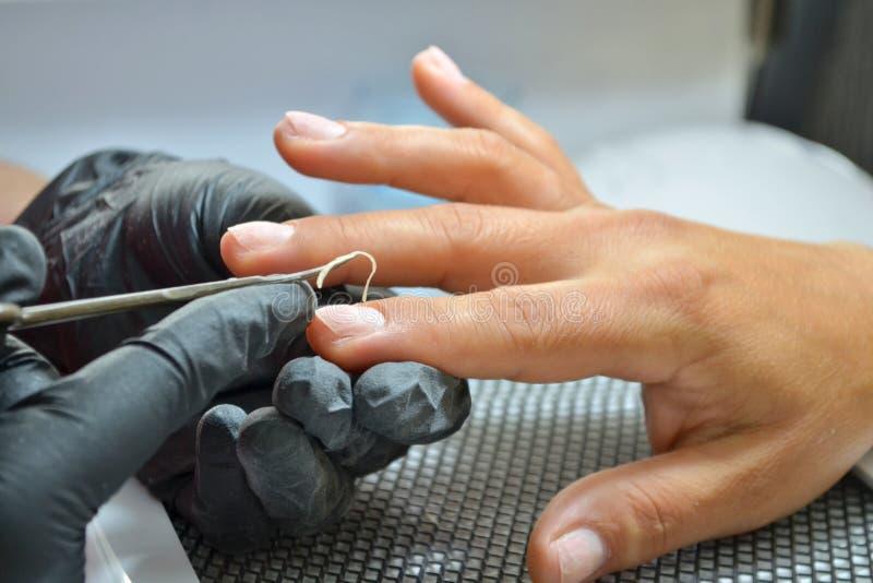 De meester van manicure in zwarte handschoenen maakt een besnoeiingsmanicure, in orde makend de opperhuid op vinger met een schaa royalty-vrije stock afbeelding