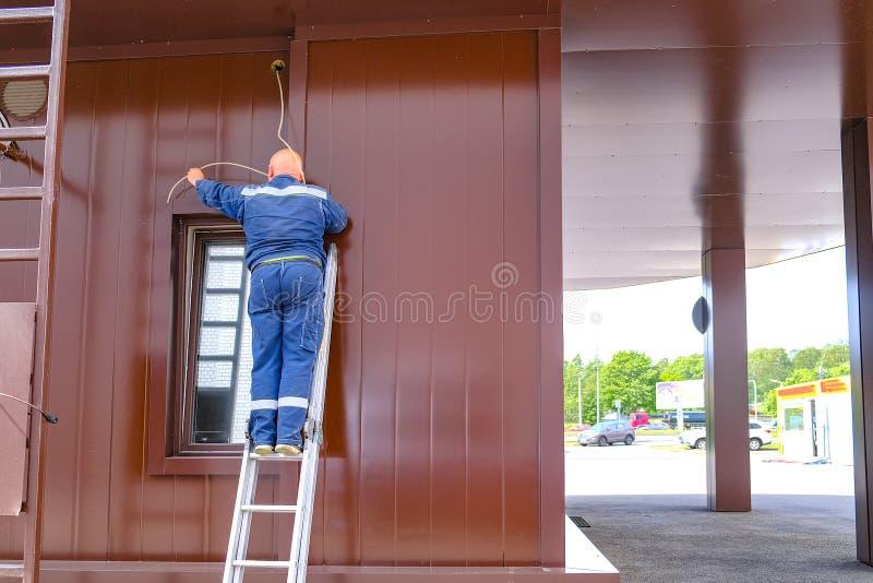 De meester van de mensenelektricien breidt een elektrische draad over het venster uit Status op een trapladder stock afbeelding