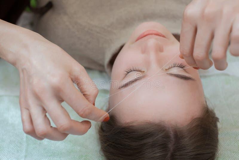 De meester verbetert make-up geeft vorm en de draad plukt wenkbrauwen in een schoonheidssalon royalty-vrije stock afbeeldingen