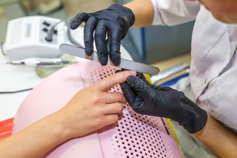 De meester in zwarte handschoenen in de salon maakt manicure tot pedicure aan de cliënt royalty-vrije stock afbeelding