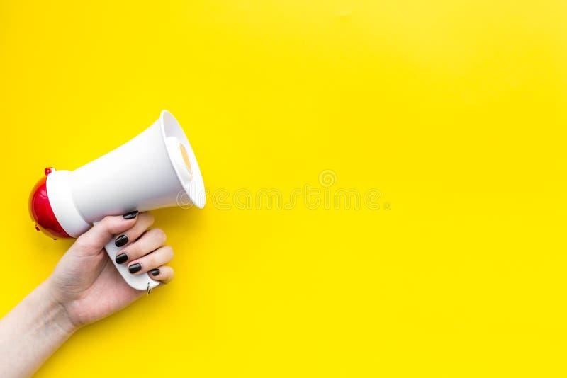 De megafoon maakt een aankondiging op de gele ruimte van het achtergrond hoogste meningsexemplaar stock afbeelding