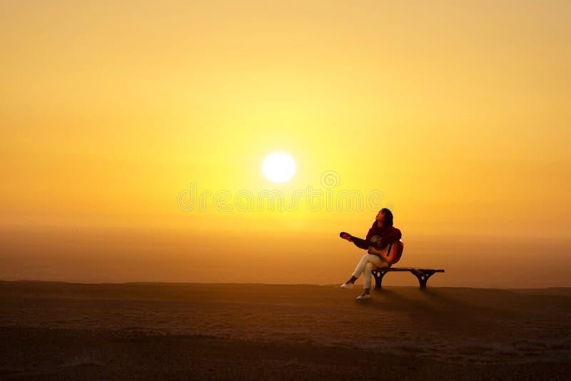 De meisje het spelen gitaar bij openluchtbanken royalty-vrije stock fotografie