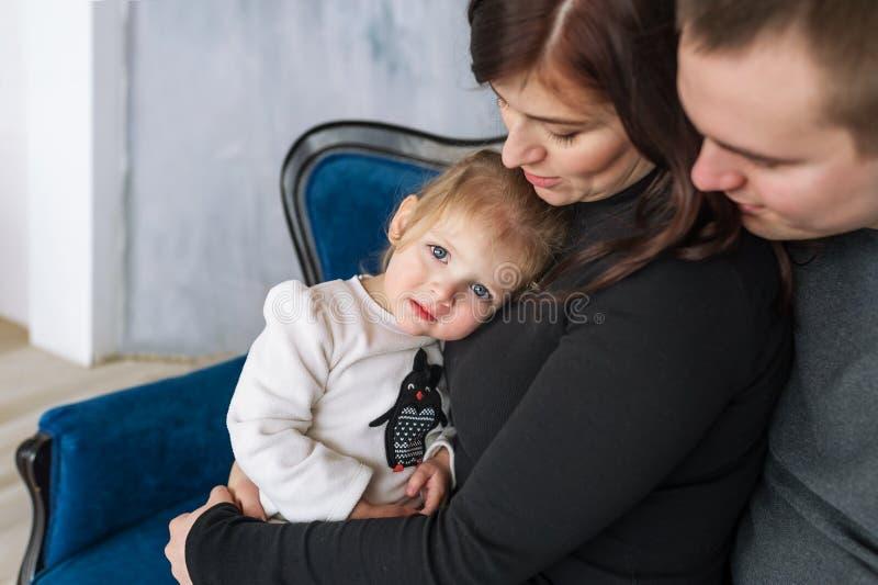 De meisjeclose-up in grepen van ouders Portret van een gelukkige familie van driepersoons stock afbeeldingen