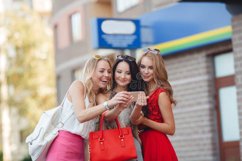 De meisjes bekijken foto's op een mobiele telefoon stock afbeeldingen