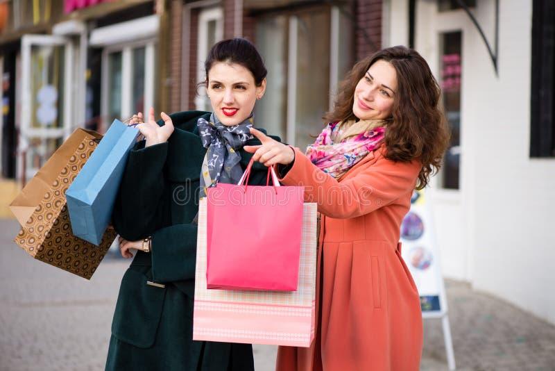 De meisjes bespreken te kopen wat terwijl het winkelen royalty-vrije stock afbeeldingen